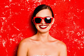 Glamorous happy girl with red lips with spectacles against the red background