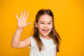 Portrait of her she nice-looking cute attractive lovely pretty cheerful cheery positive pre-teen girl waving hi hello greetings I'm here isolated over bright vivid shine yellow background