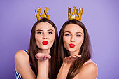 Close up portrait two people beautiful she her models chic ladies hands arms palms send air kisses servants gold crowns head wear summer colorful dresses isolated purple violet bright background