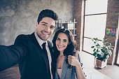 Photo of two partners making selfies in new workshop office raising thumb up dressed formal wear suits