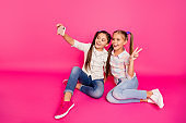 Close up photo two people little age she her girls hold hands arms telephones make take selfies v-sign sit floor  wear casual jeans denim checkered plaid shirts isolated rose vibrant background