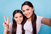 Close up photo amazing cheer beautiful two people brown haired mum mom small little daughter make take selfies flirty showing v-sign excited wear white t-shirts isolated bright blue background