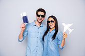 Photo of funny guy and lady holding plane tickets advice buy hot tour for low prices wear casual outfits isolated grey color background