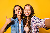 Close up photo cheerful positive stylish ladies advertise travel summer feedback decide choose advice recommend suggest excited satisfied checked beautiful jeans shirts  isolated yellow background