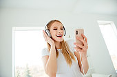 Close up photo of beautiful charming funny funky lady have holidays use user apps sing sound tracks headset laugh feel rejoice candid playful wear modern cotton clothing in apartment