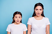 Close up photo pretty two people brown haired mum small little daughter eyes mouth opened frightened by children clothes prices wearing white t-shirts isolated bright blue background