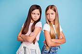 Portrait of two people nice cute lovely attractive sad mad offended gloomy straight-haired pre-teen girls standing back to back folded arms isolated over blue pastel background