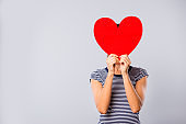 Close up photo beautiful amazing she her lady hide facial expression big large red paper heart shape figure postcard guess who game boyfriend wear blue white striped t-shirt isolated grey background