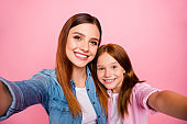 Close up photo of charming girls having long haircut making photo isolated over pink background
