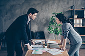 Photo of two partners seriously looking eyes competitive report standing near table workshop table
