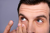 Close up cropped view photo of concentrated man use correction medical doctors office service want perfect vision forehead he his eyebrows isolated grey background