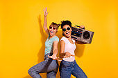 Portrait of beautiful positive cheerful content student enjoy active journey holiday beach hold hand sing wavy curly top-knot trendy style stylish t-shirt jeans specs funky isolated yellow background