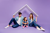 Family portrait of three members sitting floor under new roof wear casual clothes isolated purple background