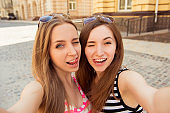 Two beautiful girl making selfie photo and showing tongue