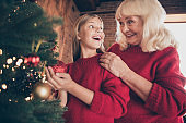 Close-up portrait of nice attractive glad excited cheerful cheery granny pre-teen grandchild hanging toys on fir having fun celebrating at decorated industrial brick wood loft style interior house