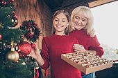 Portrait of nice attractive lovely charming cute cheerful cheery dreamy granny pre-teen grandchild hanging toys on fir spending day at decorated industrial brick wood loft style interior house