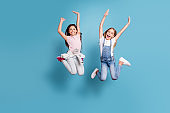 Full length body size view of two people nice-looking lovely attractive cheerful carefree straight-haired pre-teen girls having fun party overjoy great weekend isolated over blue pastel background