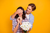 Close up photo of pair in love he him his she her lady boy flowers in hands hiding it closing eyes of dear  wearing casual plaid shirt outfit isolated on yellow background
