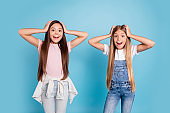 Portrait of two people nice cute amazed attractive charming cheerful funny straight-haired pre-teen girls touching head great news wow cool isolated over blue pastel background