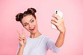 Portrait of her she nice cute fascinating attractive lovely sweet cheerful cheery girl lady holding cell in hands showing v-sign isolated over pastel pink background