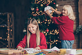 Portrait of nice attractive creative talented cheerful granny pre-teen grandchild hanging paper flake creating festive decor on table decorated industrial brick wood loft style lights interior house