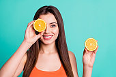 Close up photo beautiful amazing her she lady hold arms hide one eye citrus useful slices products advertising nutrition freshness wear casual orange tank-top isolated bright teal turquoise background