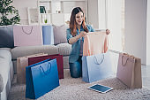 Full size photo of excited cheerful red hair girl sit on comfort floor carpet with many different bags hold her new purchase impressed scream wow omg present gift after summer holidays indoors