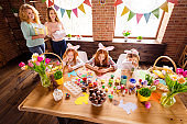 Close up photo three children make decorate eggs easter symbols children day two mom bring gift boxes look delighted cute sweet look table full craft sit big wooden table floor
