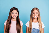 Close-up portrait of two people nice-looking sweet tender attractive beautiful cheerful straight-haired girls siblings isolated over blue pastel background
