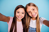 Self-portrait of two people nice-looking cute shine lovable lovely tender cheerful straight-haired pre-teen girls having fun day daydream free spare time isolated over blue pastel background