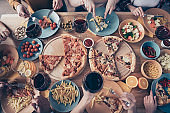 Cropped close up top above high angle view photo festive company nice social crowd event birthday members beverage sit table full fast food meals shirts formal-wear sweater pullover loft room indoors