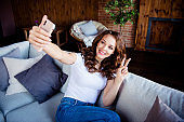 Portrait of her she nice-looking attractive lovely charming gorgeous cheerful wavy-haired girl sitting on sofa taking making selfie showing v-sign at industrial loft wooden brick style interior