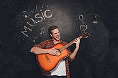 Young happy man play on guitar and singin against the background of chalkboard