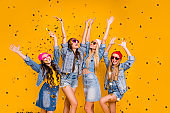 Photo of beautiful crazy little victorious excited having fun pretty mothers and daughters raising fists up in air enjoying delight isolated yellow background