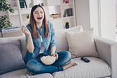 Photo of amazing lady watching favorite humorous tv show eating popcorn laughing out loud sitting comfy sofa wearing jeans clothes apartment indoors
