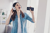 Photo of pretty lady with telephone in hands earflaps on ears singing loudly homey mood standing near sofa wearing jeans clothes apartment indoors