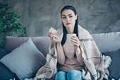 Photo of exhausted lady with cup and napkin caught cold drinking medicine from flu covered with blanket wearing pullover and jeans sitting sofa