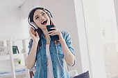 Photo of pretty lady with telephone in hands earflaps on ears recording home single for music studio standing near sofa wearing jeans clothes apartment indoors