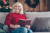 Portrait of her she nice attractive lovely cheerful cheery gray-haired granny sitting on divan reading book spending vacation at industrial loft style interior house indoors