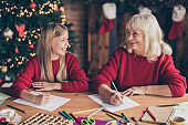 Portrait of nice attractive glad positive cheerful cheery granny pre-teen grandchild writing Santa want wish gift list on table at decorated industrial brick wood loft style lights interior house