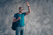 Close up photo amazing he him his dark skin macho handsome last study year look empty space wave arm palm friends cheerful glad meeting wear specs casual blue t-shirt isolated grey background