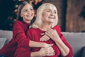 Close-up portrait of nice attractive lovely sweet careful affectionate cheerful cheery granny grandchild sitting on cosy divan holding hands cuddling at decorated industrial loft style interior house