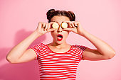 Close-up portrait of nice cute charming attractive glamorous lovely funny comic teen girl in striped t-shirt covering eyes with colorful delicious snack opened mouth isolated over pink background