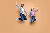 Hooray. Full size photo of two people crazy lady guy jumping high celebrating best win of football team raising fists wear casual checkered jeans outfit isolated beige background