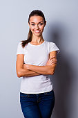 Vertical close up photo beautiful she her lady hands arms crossed self-confident easy-going reliable business person wondered look wear jeans denim casual white t-shirt isolated grey background