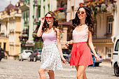 Portrait of cute pretty teen teenagers students modern feel satisfied have promenade trip long hair moving dressed in colorful skirts wear fashionable eyeglasses in center