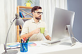 Man in glassses drinking coffee while working in office with pc