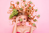Close up top above high angle view photo beautiful she her lady lying down grape fruits in long curly wavy hair cover eye kiwi slice healthy lifestyle eating feeding isolated pink background