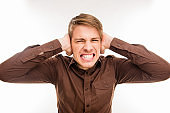 Close up photo of annoyed young man plugging ears with hands