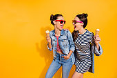 Photo of two brunette hair lady in glasses spectacles isolated on yellow background hold sugar tasty yummy delicious sweet appetiser snack in hands look each other make beaming hollywood toothy smile